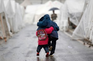 Syrian boys walk shoulder to shoulder in the rain at the Boynuyogun refugee camp on the Turkish-Syrian border in Hatay province